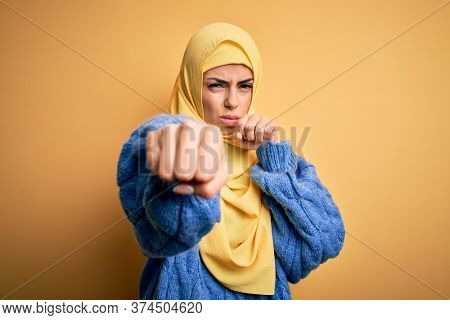 Young beautiful brunette muslim woman wearing arab hijab over isolated yellow background Punching fist to fight, aggressive and angry attack, threat and violence