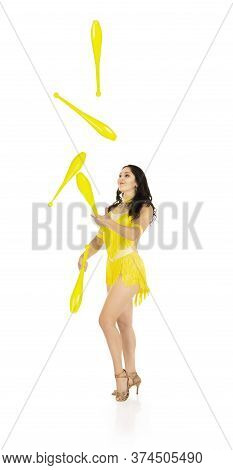 A Juggler, A Circus Performer, A Young Woman In A Yellow Suit With Dark Hair, Performs On A White Ba