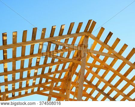 Yellow Wooden Rafters Against The Blue Sky In The Sunset Light. The Construction Of The Roof Of A Re