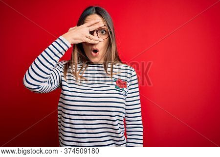 Young beautiful blonde woman with blue eyes wearing glasses standing over red background peeking in shock covering face and eyes with hand, looking through fingers with embarrassed expression.