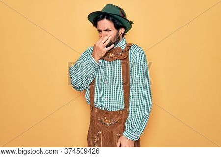 Young handsome man wearing tratidional german octoberfest custome for Germany festival smelling something stinky and disgusting, intolerable smell, holding breath with fingers on nose. Bad smell