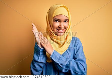 Young beautiful woman with curly hair wearing arab traditional hijab over yellow background clapping and applauding happy and joyful, smiling proud hands together