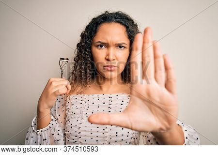 Young beautiful woman with curly hair holding eyelases curler over white background with open hand doing stop sign with serious and confident expression, defense gesture
