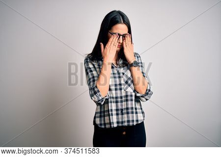 Young brunette woman with blue eyes wearing casual shirt and glasses over white background rubbing eyes for fatigue and headache, sleepy and tired expression. Vision problem