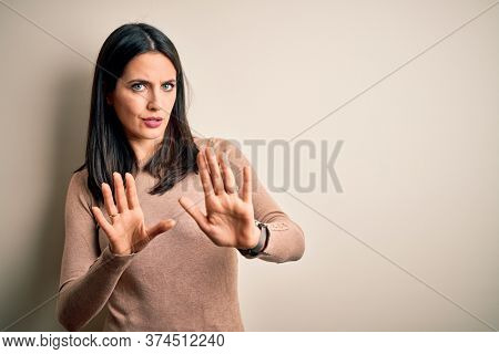 Young brunette woman with blue eyes wearing casual sweater over isolated white background Moving away hands palms showing refusal and denial with afraid and disgusting expression. Stop and forbidden.