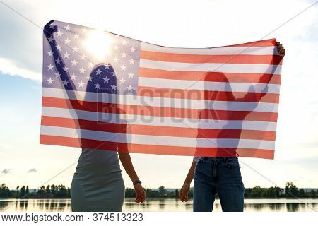 Silhouette Of Two Young Friends Women Holding Usa National Flag In Their Hands Standing Together Out
