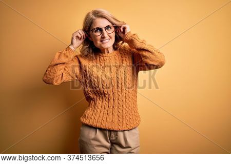Middle age beautiful blonde woman wearing casual sweater and glasses over yellow background Smiling pulling ears with fingers, funny gesture. Audition problem