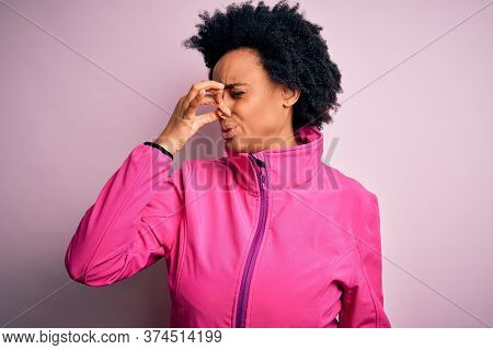 Young African American afro sportswoman with curly hair wearing sportswear doin sport smelling something stinky and disgusting, intolerable smell, holding breath with fingers on nose. Bad smell
