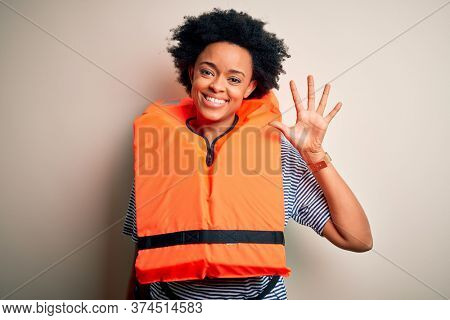 Young African American afro woman with curly hair wearing orange protection lifejacket showing and pointing up with fingers number five while smiling confident and happy.