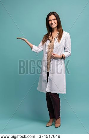 Young Medical Doctor Woman Presenting And Showing Copy Space For Product Or Text. Caucasian Female M
