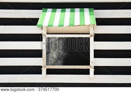 Small Aged White Retro Chalk Board Hanging On Black And White Wooden Wall. Concept For Advertising D