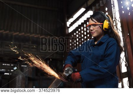 Young Diverse Female Mechanic Using Factory Equipment To Cut Metal Wearing Safety Workwear And Equip