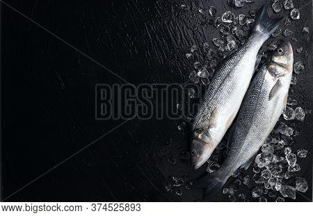 Fresh Seabass Fish On Ice On Black Background
