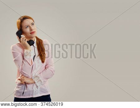 Skeptical Woman Talking On Phone Deciding What To Answer Isolated On Gray Studio Background