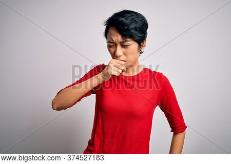 Young beautiful asian girl wearing casual red t-shirt standing over isolated white background feeling unwell and coughing as symptom for cold or bronchitis. Health care concept.