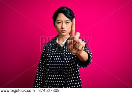 Young beautiful asian girl wearing casual jacket standing over isolated pink background Pointing with finger up and angry expression, showing no gesture