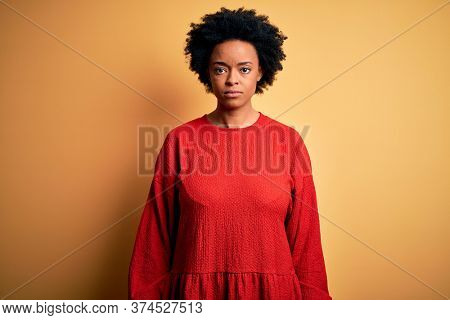 Young beautiful African American afro woman with curly hair wearing casual sweater with serious expression on face. Simple and natural looking at the camera.