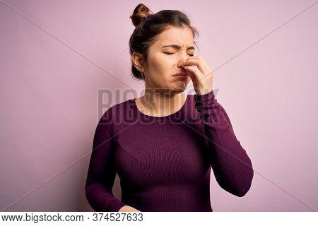 Beautiful young woman wearing casual bun hairstyle over pink isolated background smelling something stinky and disgusting, intolerable smell, holding breath with fingers on nose. Bad smell