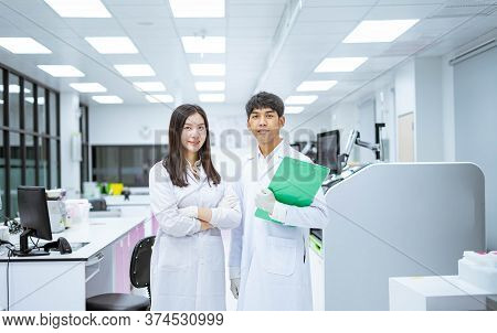 Two Young Smiling Scientist In White Lab Coat Standing With Automation Blood Analyzer At Medical Lab