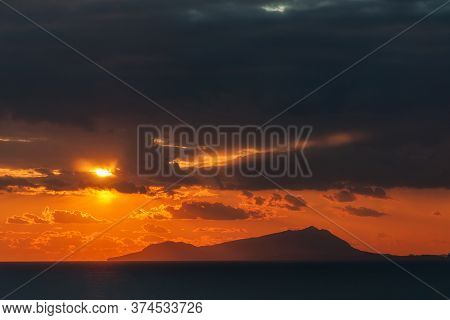 Capris Skyline At Sunset With Red Cloudy Sky, Capri Is A Wonderful Island In The Gulf Of Naples Ital