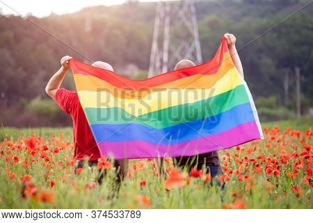 Gay couple holding a Gay Rainbow Flag over beautiful poppy field. Bisexual,gay, lesbian, transsexual symbol. Happiness, freedom and love concept for same sex couples