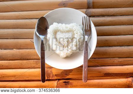 Steamed Rice In The Plate. Over Wooden Background.cooked Rice On Plate. Heart Shaped Rice On A White