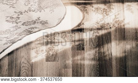 A Curtain Decorated With White Lace Which, Moved By The Light Breeze, Casts Its Shadow On A Parquet