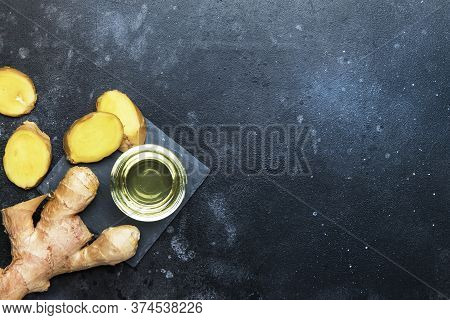 Ginger Oil And Fresh Ginger Root, Gray Kitchen Table, Copy Space, Top View