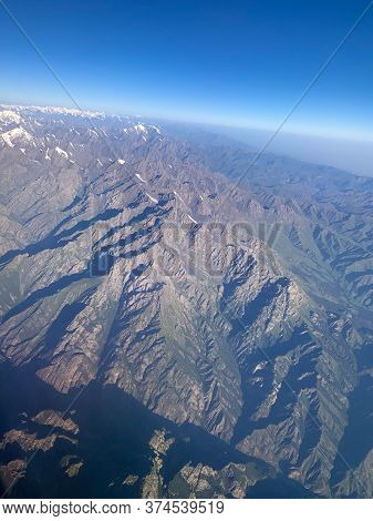The View From The Airplane, Flying Over The Mountains Area. Aerial Photography