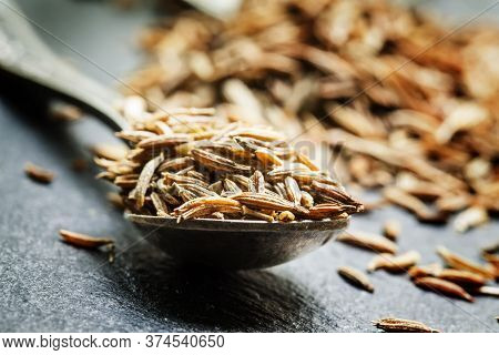 Zira Or Cumin In A Metal Spoon On A Dark Background, Close-up, Selective Focus, Shallow Depth Of Fie