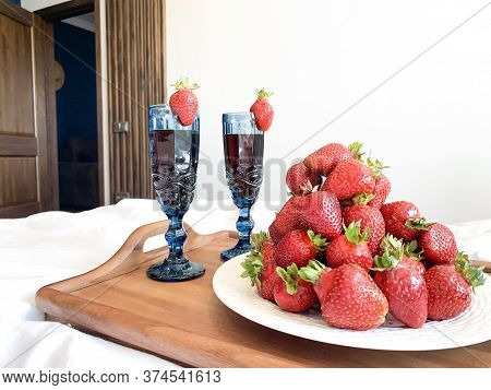 Strawberries On A Wooden Tray. Rest At The Hotel, White Bedding, Blue Glasses With Strawberries, Fru