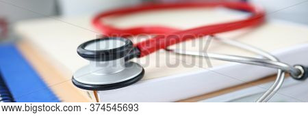 Close-up Of Red Stethoscope Laying On Papers. Instrument To Examine Breath Of Patient. Doctor Office