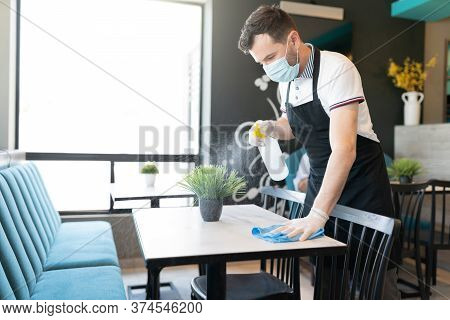 Male Worker Cleaning Table With Disinfectant In Restaurant During Coronavirus Outbreak