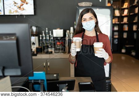 Female Staff Wearing Face Mask And Gloves While Serving Coffee In Cafe