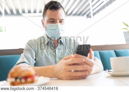 Mid Adult Man Using Smartphone In Coffee Shop During Coronavirus Outbreak