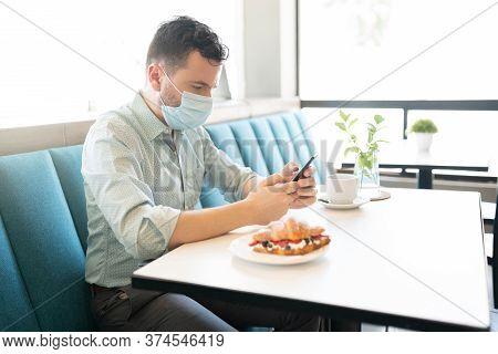 Caucasian Mid Adult Man Using Mobile Phone In Cafe During Coronavirus Crisis