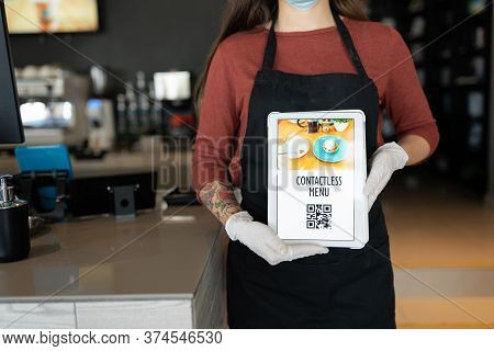 Midsection Of Female Staff Showing Contactless Menu Qr Code On Digital Tablet In Restaurant