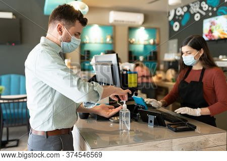 Caucasian Man Applying Disinfectant On Hand At Checkout Counter In Cafe During Coronavirus Crisis