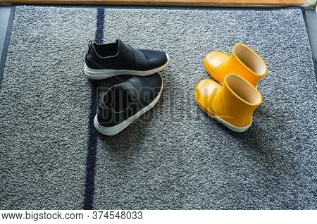 Close Up View Of Yellow And Black  Pair Summer Kid Shoes On Mat Near Entrance Door.  Kid Shoes Conce
