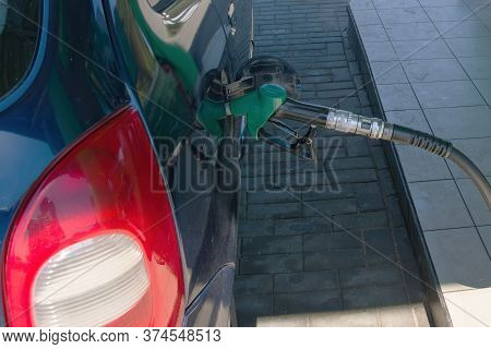 Filling Gun Into The Hole Of Empty Gasoline Tank Of Car On Diesel Fueling. Filling Station Concept.