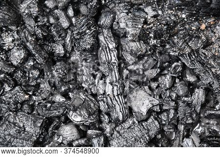 Selective Focus Of Ash Coal Background Of Charcoal Pieces Cooling Down. Texture Of Burnt Wastes Afte