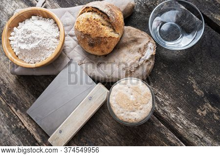 Still Life Setting Of Sourdough Bread Bun And Ingredients - Flour, Starter Yeast And Water. On Rusti
