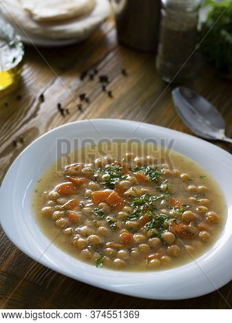 Vegetarian Thick Cheakpea Soup With Corrots And Greens In White Plate On Wooden Table With Ingredien
