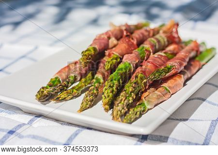 Green Organic Asparagus Baked With Bacon. Cooked Asparagus Officinalis On White Plate On The Table.