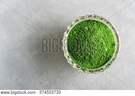 Shredded Chlorella Or Spirulina In A Glass Cup On Grey Concrete. Top View.
