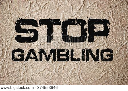 Stop Gambling Phrase Sign On Old Texturized Wall. Qut Addiction Concept On Grunge Background