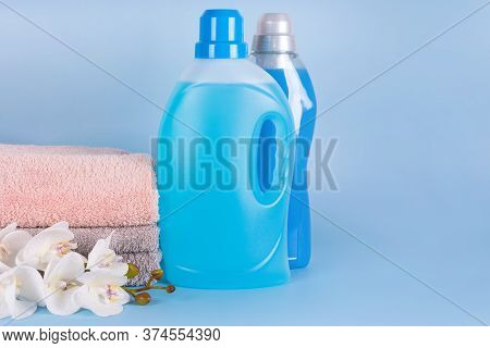Bottles Of Detergent And Fabric Softener With Clean Towels And Orchid Flowers On Blue Background. Co
