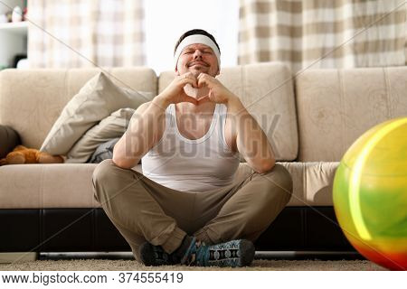 Guy Sits At Home Carpet Meditates And Shows Heart. Get Out Your Usual Comfort Zone. Relaxing Therapy