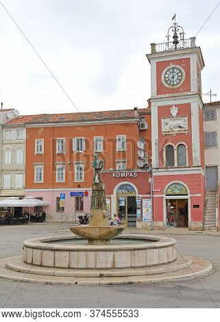 Rovinj, Croatia - October 15, 2014: Water Fountain With Sculture And Clock Tower At Picturesque Town