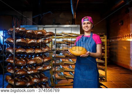 Professional Baker - A Young, Pretty Woman In A Jeans Apron Holds Fresh Bread Against The Background